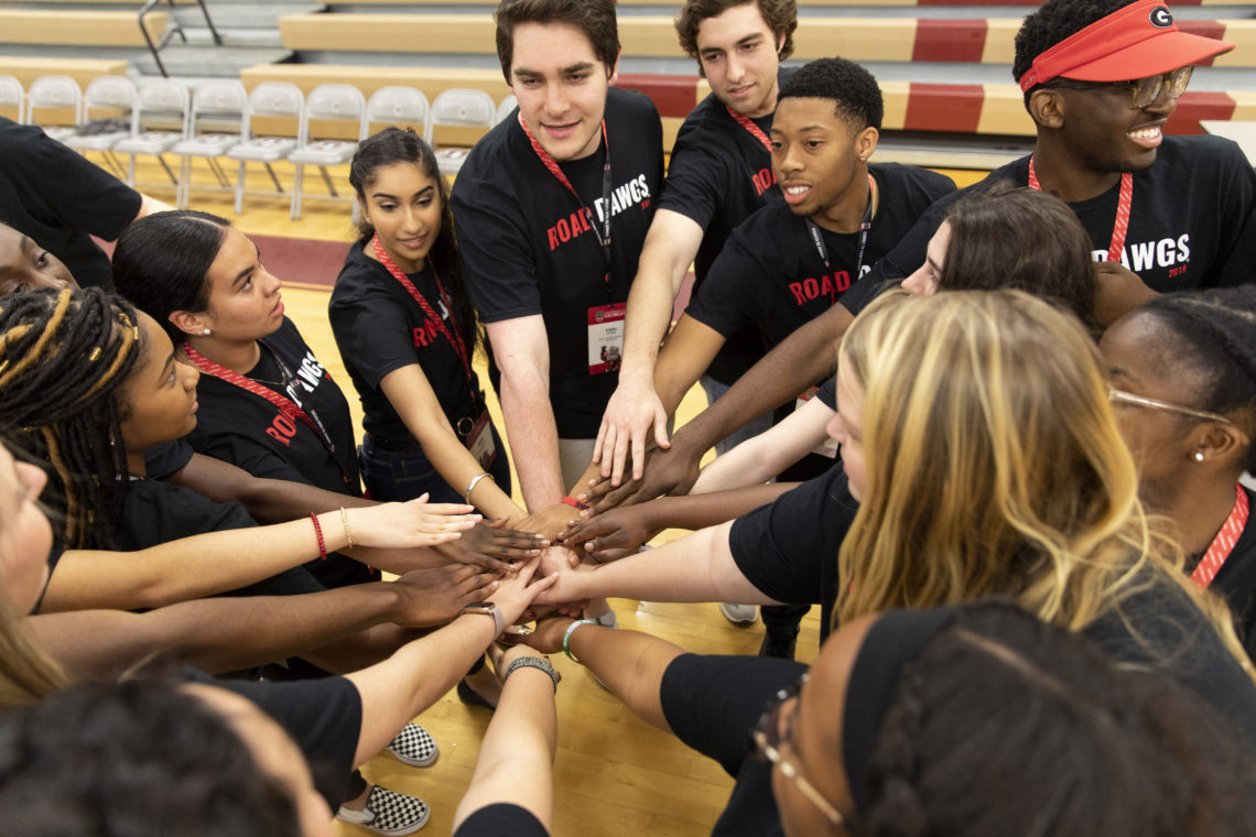 Road Dawg students put their hands together in unison in the gymnasium of Dougherty Comprehensive High School before the start of their program.